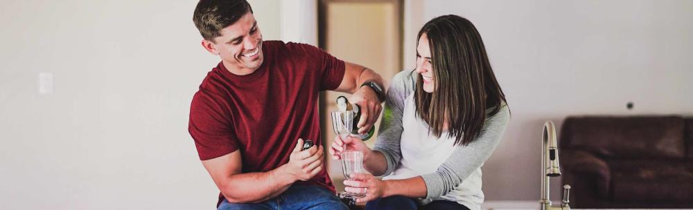foto - koppel drinkt lachend champagne in nieuw huis