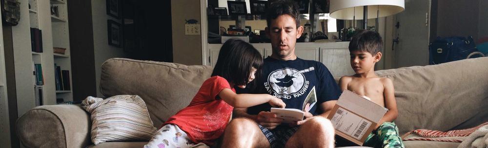 foto - Man leest brochures in zetel met kinderen